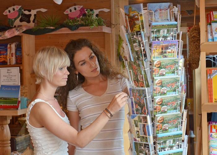 Gäste kaufen Postkarten im Hofladen auf dem Kur-Camping Arterhof